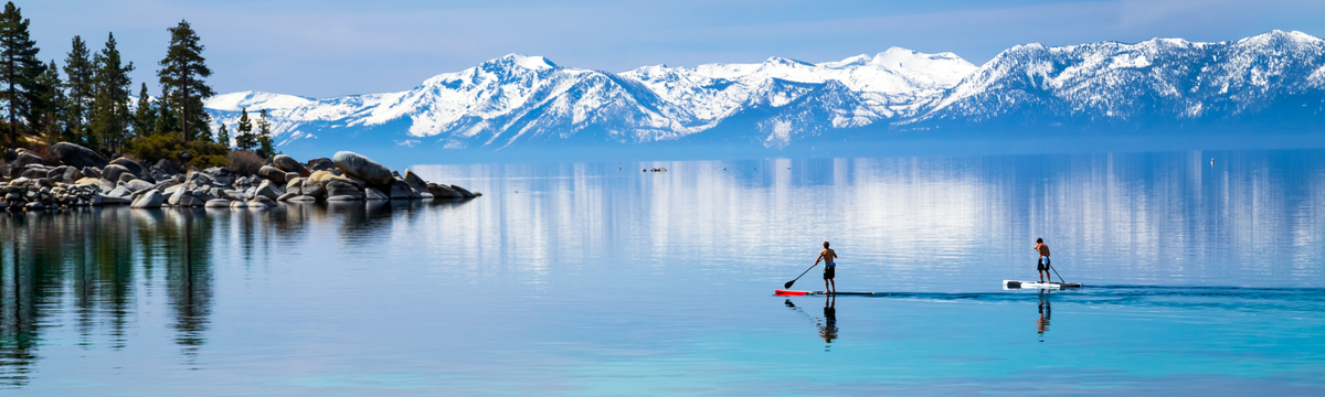 Paddleboarders on Lake Tahoe with snow-capped mountains in the background