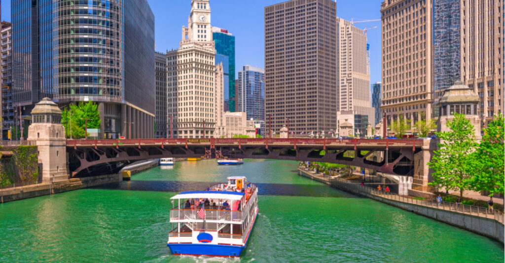 View of a boat on the Chicago River with a bridge and skyscrapers in the background.
