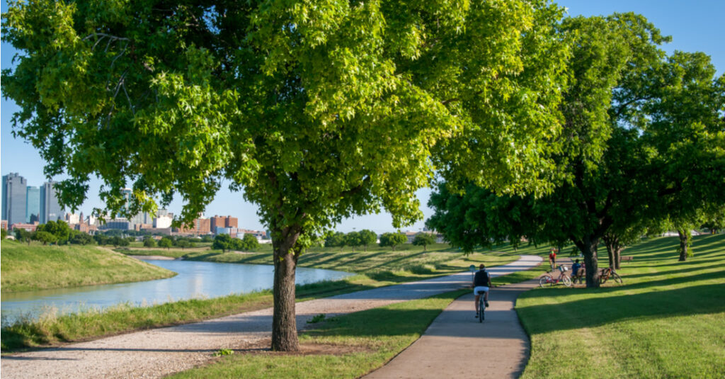 A cyclist rides along the Trinity Trails next to the Trinity River with the Fort Worth, Texas, skyline in the background.