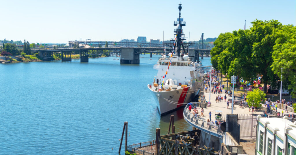 People walk along the Willamette River, past a coastguard ship, in Governor Tom McCall Waterfront Park in Portland, Oregon.