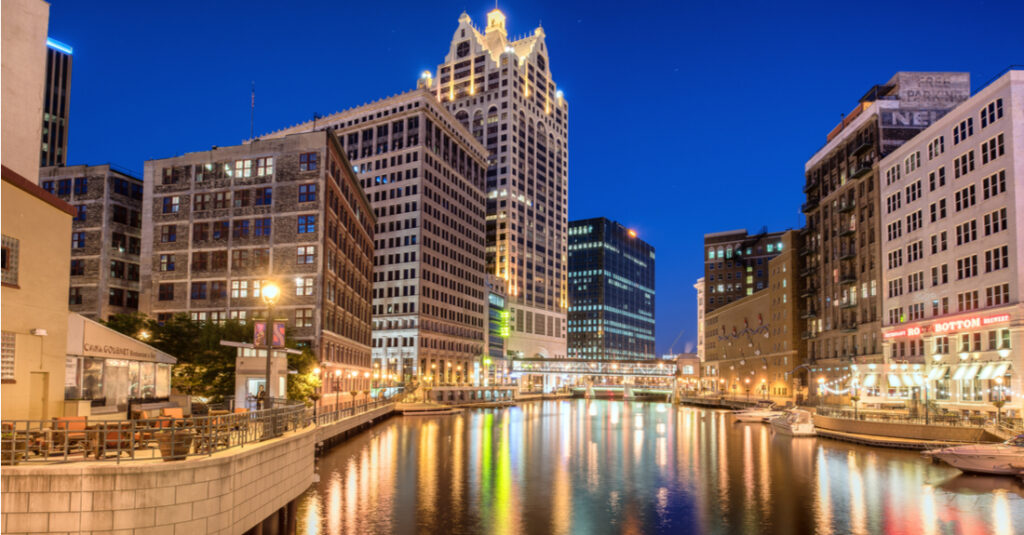 The Milwaukee RiverWalk and the downtown Milwaukee skyline at night, with city lights reflecting on the water.
