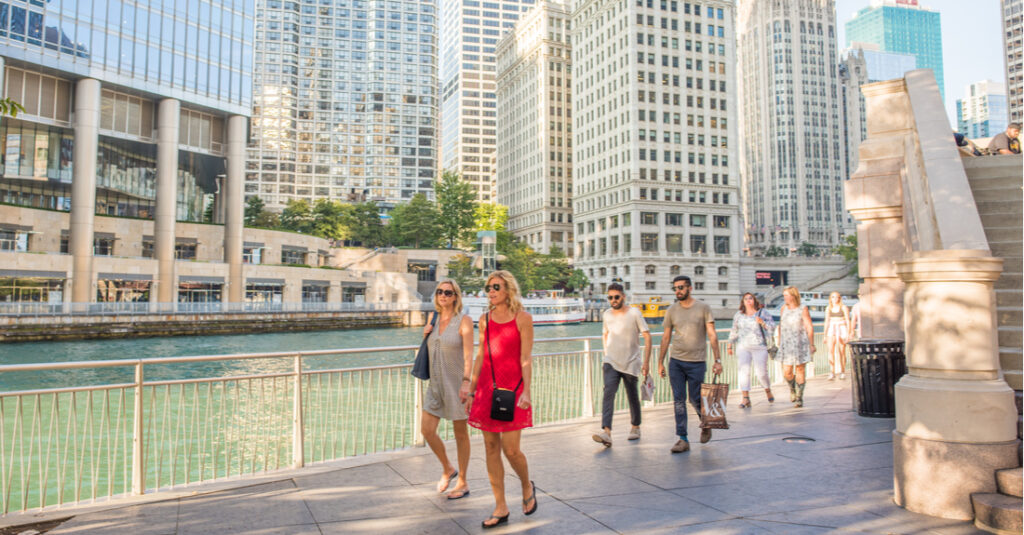 A group of people walking along the Chicago Riverwalk in the summertime.